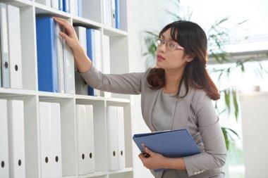 businesswoman taking binder from shelf
