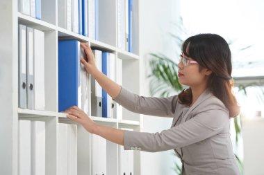 businesswoman searching binder on shelf