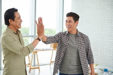 man giving high five to coworker