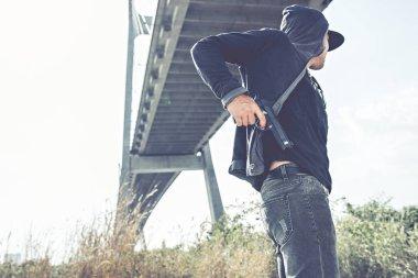 Gangster putting pistol into back pocket