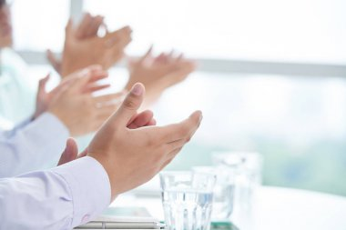 clapping business executives at meeting