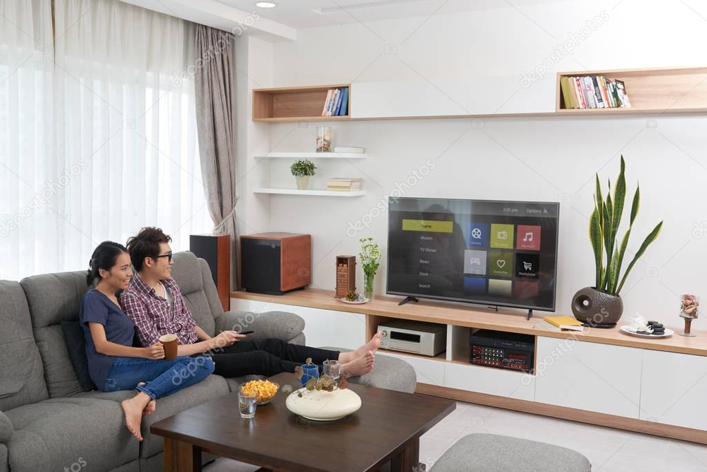 Coppia seduta sul divano e guardare la tv foto stock - Divano al centro della stanza ...