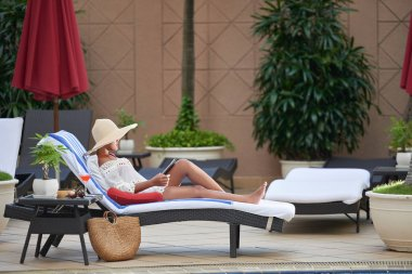 woman in straw hat reading e-book