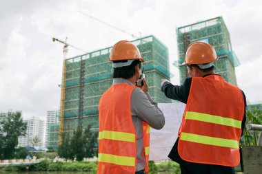 Contractor and engineer examining construction site