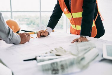 Engineers working on new building blueprint