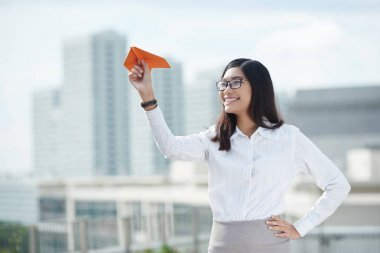 woman launching paper airplane