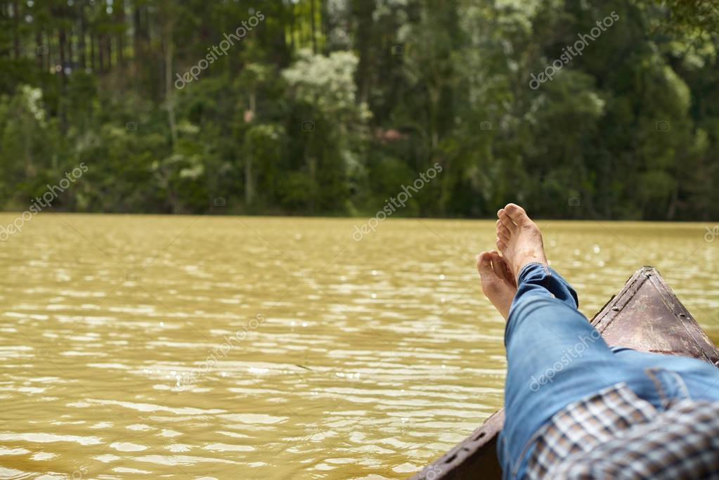 Man relaxing lying in boat