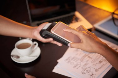 Business woman paying with smartphone