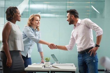 Man greeting female business partners