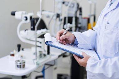 Doctor filling medical case history