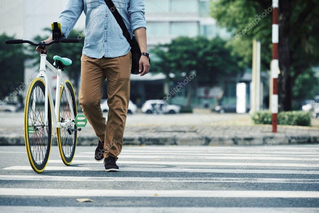 Man crossing road with bike