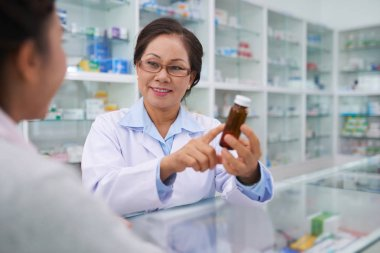 Pharmacist and customer discussing medicine