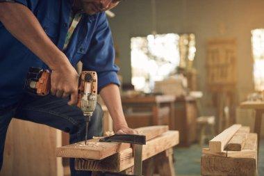 carpenter drilling plank