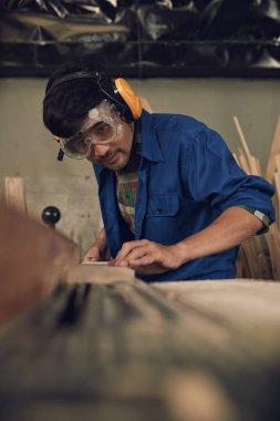 Carpenter in goggles cutting wood