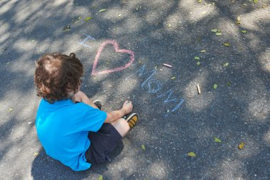 boy writing words with colorful chalks