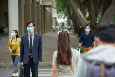 Portrait of middle-aged Asian businessman wearing facial mask in order to protect himself from smog while crossing road with other people stock vector