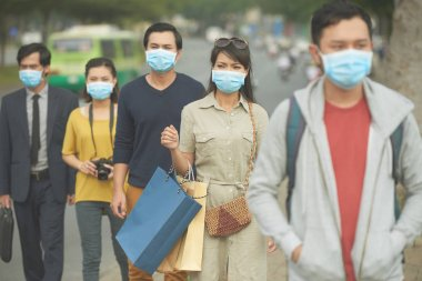Citizens walking on the street in masks because of danger of epidemic stock vector