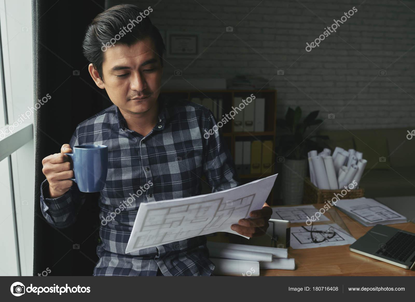 Professional asian engineer drinking coffee looking blueprint professional asian engineer drinking coffee looking blueprint stock photo malvernweather Choice Image