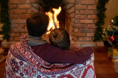 Rear view of affectionate couple embracing and looking at fireplace on Christmas Eve