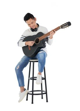 Talented smiling Asian man sitting on stool and playing guitar