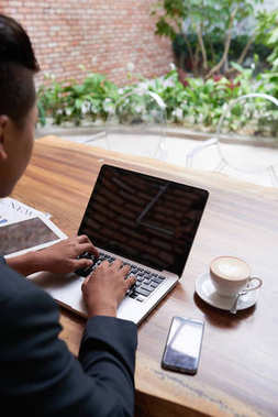 Back view portrait of successful young businessman using laptop while working in cafe via wi-fi network