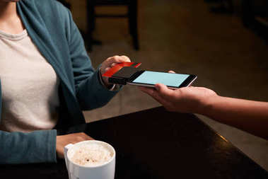 Female customer swiping card to pay for the coffee