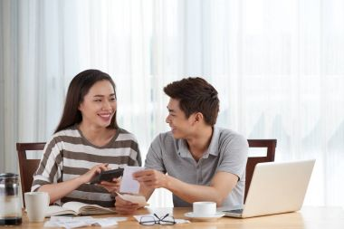 woman and her husband managing family budget while sitting at wooden table at home