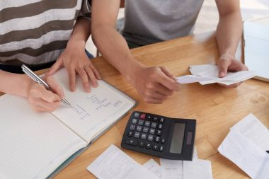 family keeping records of expenses, woman taking notes in notepad