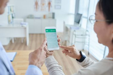 Over shoulder view of doctor and patient using smartphone