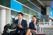 Fotografie Portrét asijské muže a ženy čekají v zóně letiště odletu, pomocí digitálních zařízení