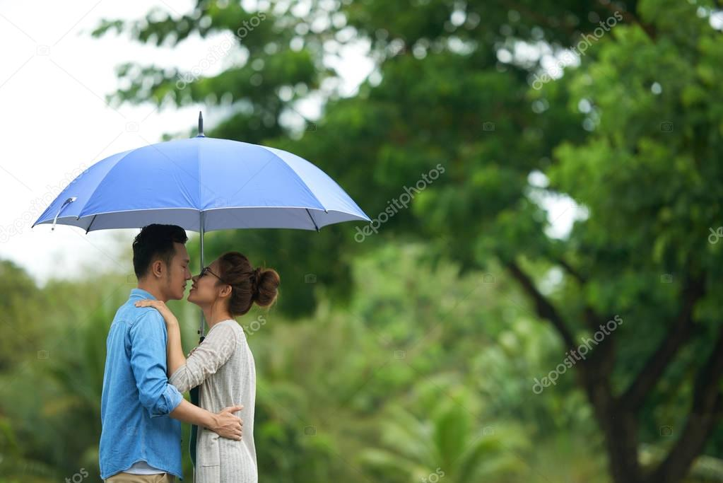 Side view portrait of young Asian couple kissing in rain, standing under umbrella