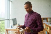 Fotografie Afro-American businessman holding digital tablet while standing in modern office with panoramic windows