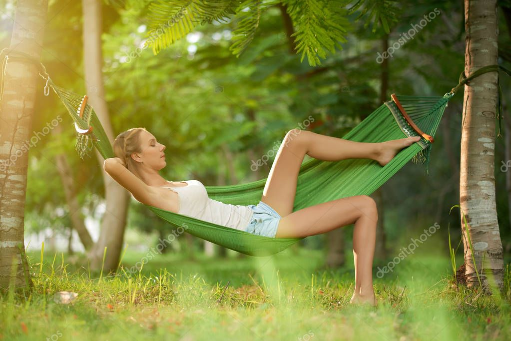 relaxed woman lying in hammock during warm sunny day