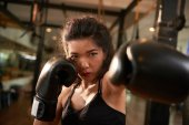 Young female fighter in boxing gloves hitting