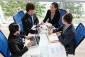 Pohled z vysokého úhlu jistý vietnamských podnikatelů zabalený v práci při sezení u stolu v prostorné zasedací místnosti s panoramatickými okny