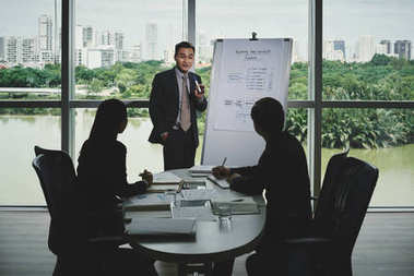 Vietnamese white collar worker presenting his start-up project to potential investors while having meeting in modern boardroom with panoramic windows