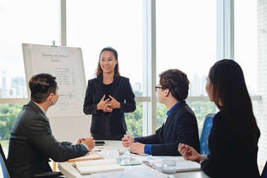 Smiling Vietnamese white collar worker holding working meeting in spacious boardroom, colleagues sitting at table and listening to her with interest