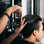 Fotografie Close-up image of barber cutting hair with professional scissors