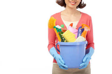 smiling housewife holding bucket with cleaning utensils in hands while standing against white background