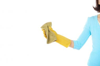 housewife wearing rubber gloves holding rag in hand while standing against white background