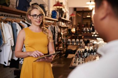 Beautiful blonde woman in clothes shop using digital tablet stock vector