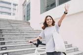 Fotografie Šťastné mladé Asijské žena s kolo mávat rukama