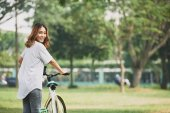 Young woman with bicycle turning back and looking at camera