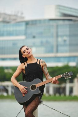 Portrait of alternative smiling girl with many tattoos playing guitar