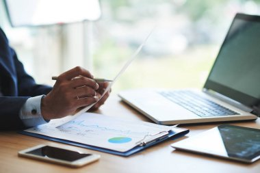 Hands of businessman analyzing financial report at is table