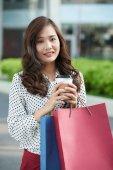Divatos fiatal nő bevásárló táskák és csésze kávé