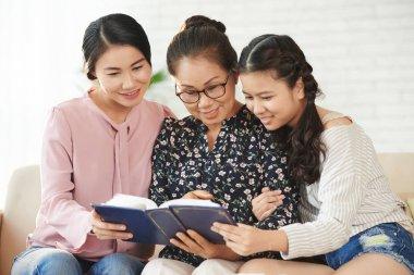 Female generation of Vietnamese family watching photos in album