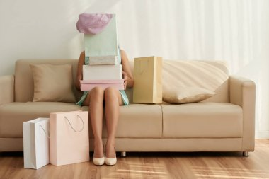 Woman sitting on sofa with many boxes on her knees