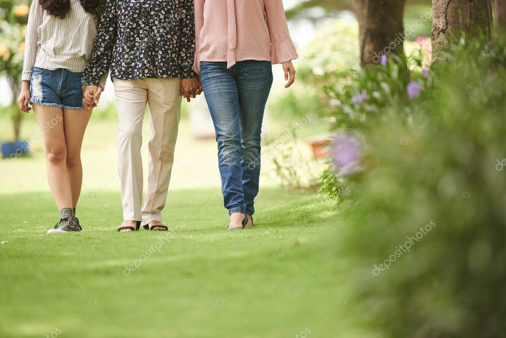 Legs of mother, daughter and granddaughter holding hands when walking outdoors