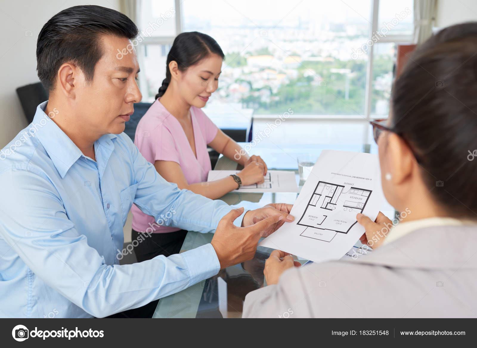 Mature vietnamese man discussing blueprint building real estate mature vietnamese man discussing blueprint building real estate agent stock photo malvernweather Images